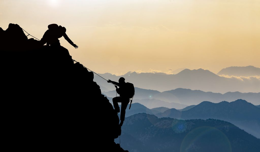 A silhouette of two people climbing a mountain, one with their arm stretched out for the other