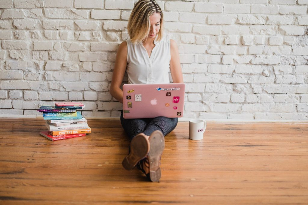 woman sitting on the ground with her laptop and a stack of books next to her